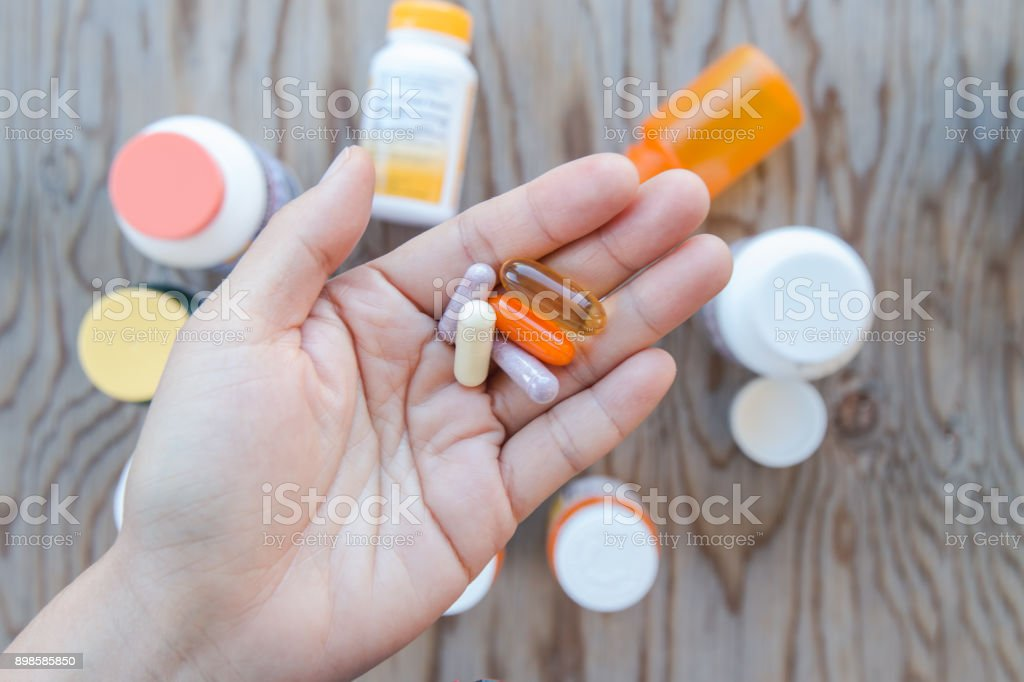 A hand holding a bunch of pills in an open palm. stock photo