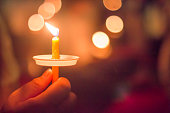 hand holding a burning candle with bokeh background