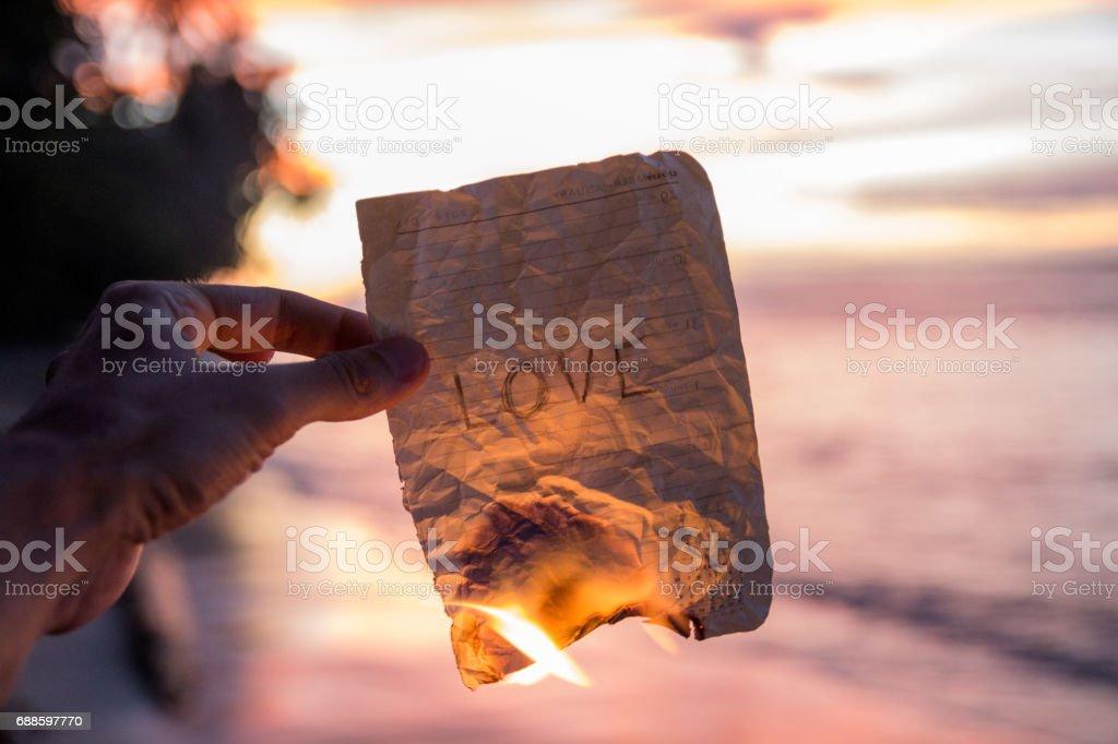 Hand som håller ett brinnande papper med ordet kärlek bildbanksfoto