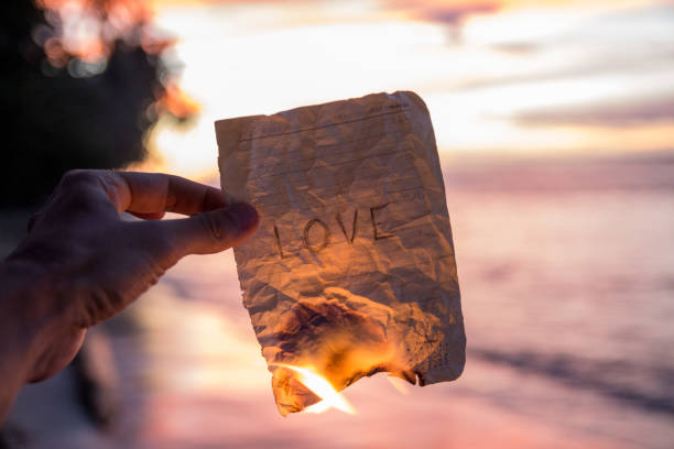 Hand holding a burning paper with word Love stock photo