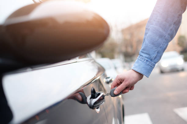 hand hält einen autoschlüssel und die autotür öffnen - mietwagen stock-fotos und bilder