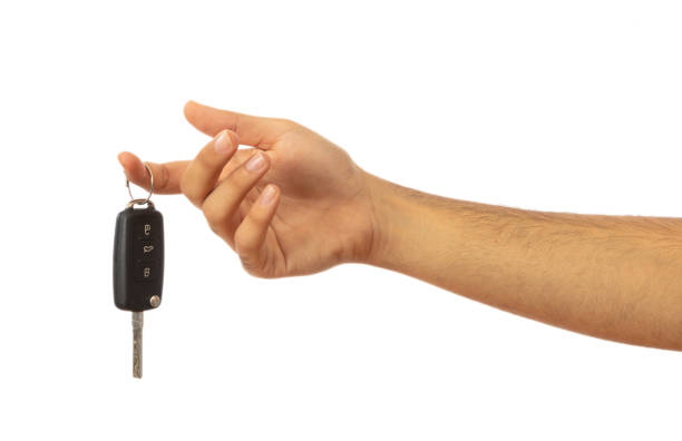 Hand holding a car key isolated on white background, clipping path Male hand holding a car key isolated on white background, clipping path car key stock pictures, royalty-free photos & images
