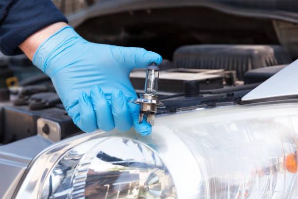 Hand hält eine Auto-Glühbirne, Scheinwerfer im Hintergrund. Scheinwerferersatzkonzept. – Foto