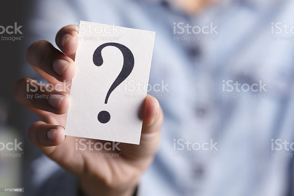 Hand holding a card with a question mark on it stock photo
