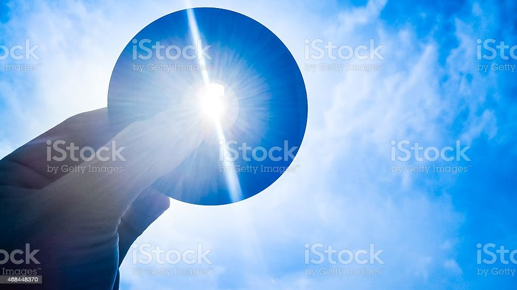 Hand holding a cd up to the sun so the sun shines through it stock photo