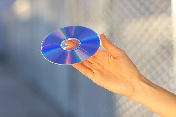 main tenant un lecteur cd/dvd et lecteur blu-ray - blu ray disc photos et images de collection