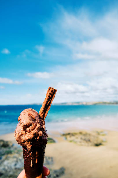 hand holding a chocolate ice cream over towan beach, newquay, cornwall on a sunny june day. - ice cream cone stock pictures, royalty-free photos & images