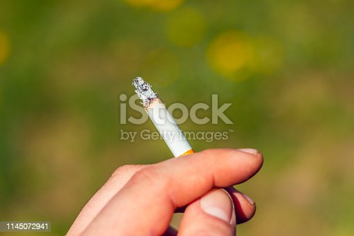 Close-up to a man's hand holding a cigarette – Human part with tobacco outdoor – Smoking or bad habit conceptual image