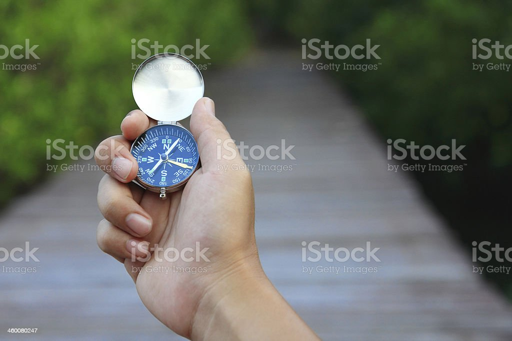Hand holding a compass facing northeast stock photo