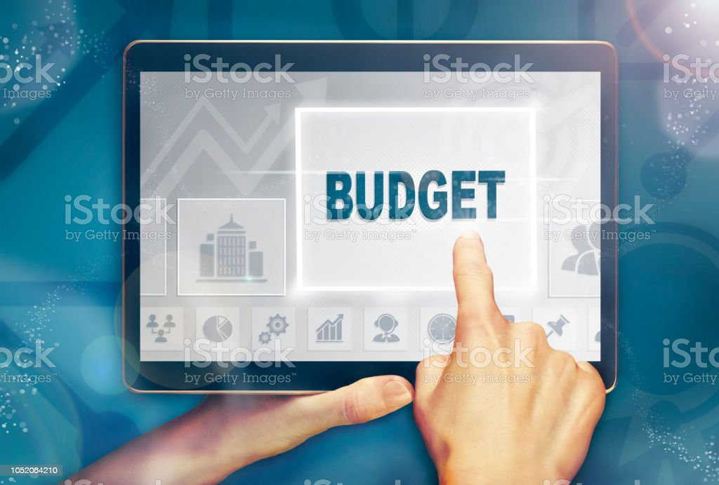 A hand holding a computer tablet and pressing a budget concept. stock photo
