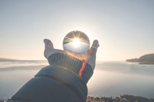 Hand holding a crystal ball in the winter sunrise stock photo