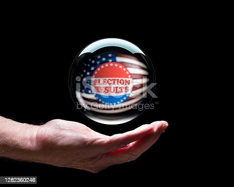 istock Hand holding a crystal glass forecasting ball to predict the result of the election 1282360246