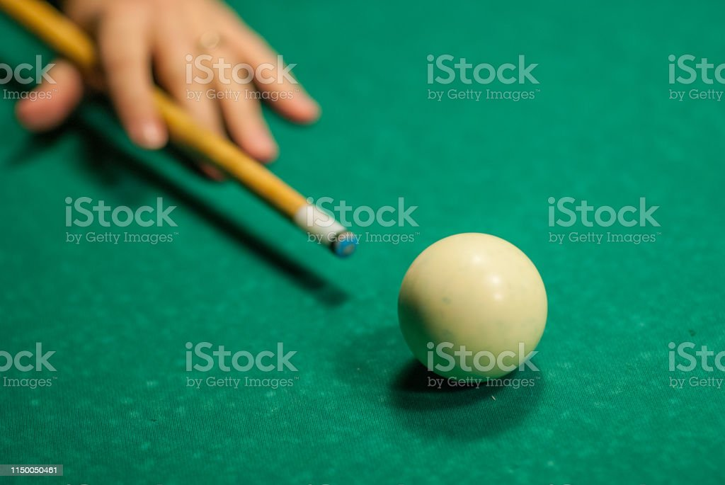 A hand holding a cue stick about to hit a white cue ball, playing...