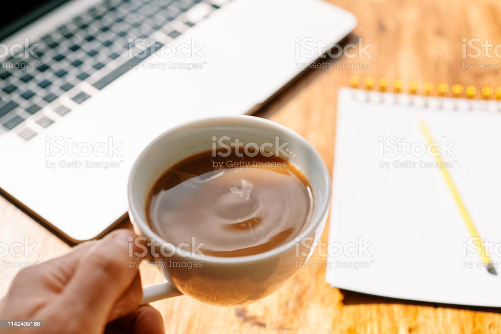 POV hand holding a cup of coffee with defocused notepad and laptop. stock photo