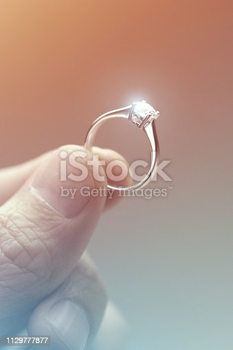 Close-up of a hand holding a diamond engagement ring.