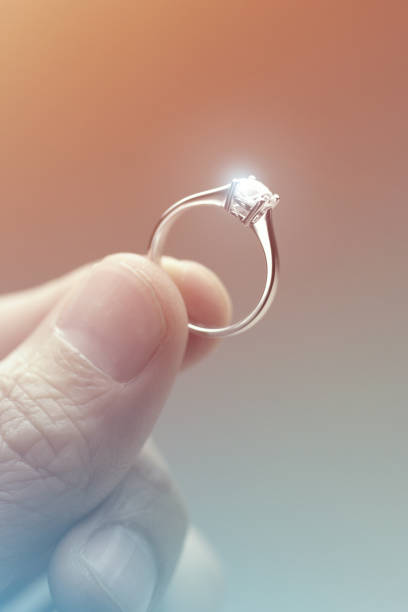 hand holding a diamond engagement ring - diamond ring hand stock pictures, royalty-free photos & images