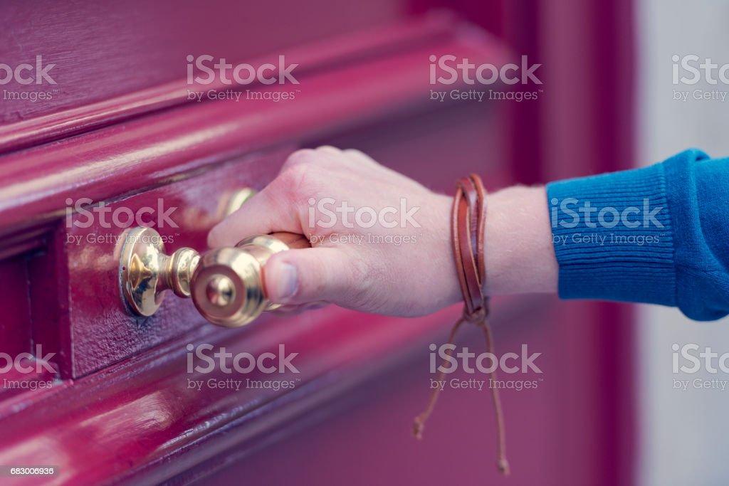 Hand holding a door knob on the red wooden door foto de stock royalty-free