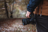 Hand holding a DSLR camera in a forest in autumn