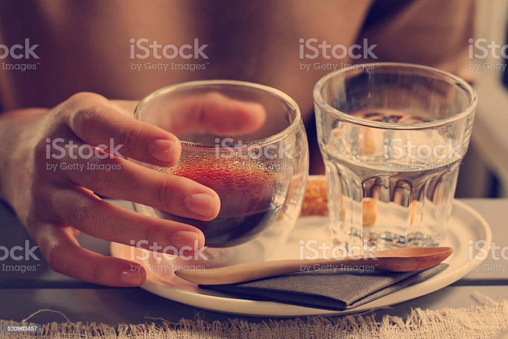 hand holding a freshly brewed cup of hot black coffee stock photo