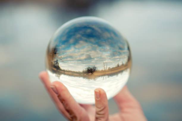 hand hält eine glaskugel mit reflexion der see - wettervorhersage deutschland stock-fotos und bilder