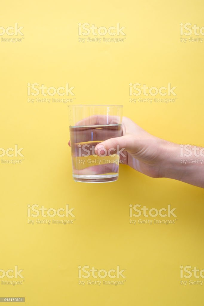 Hand holding a glass full of water on yellow background stock photo