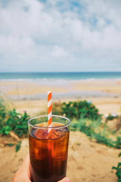 pov hand holding a glass of black iced coffee at fistral beach on a summers day. - iced coffee stock photos and pictures