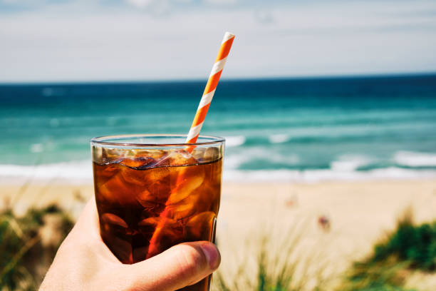 hand holding a glass of iced black coffee above fistral beach, newquay on a hot sunny summers day. - iced coffee stock pictures, royalty-free photos & images