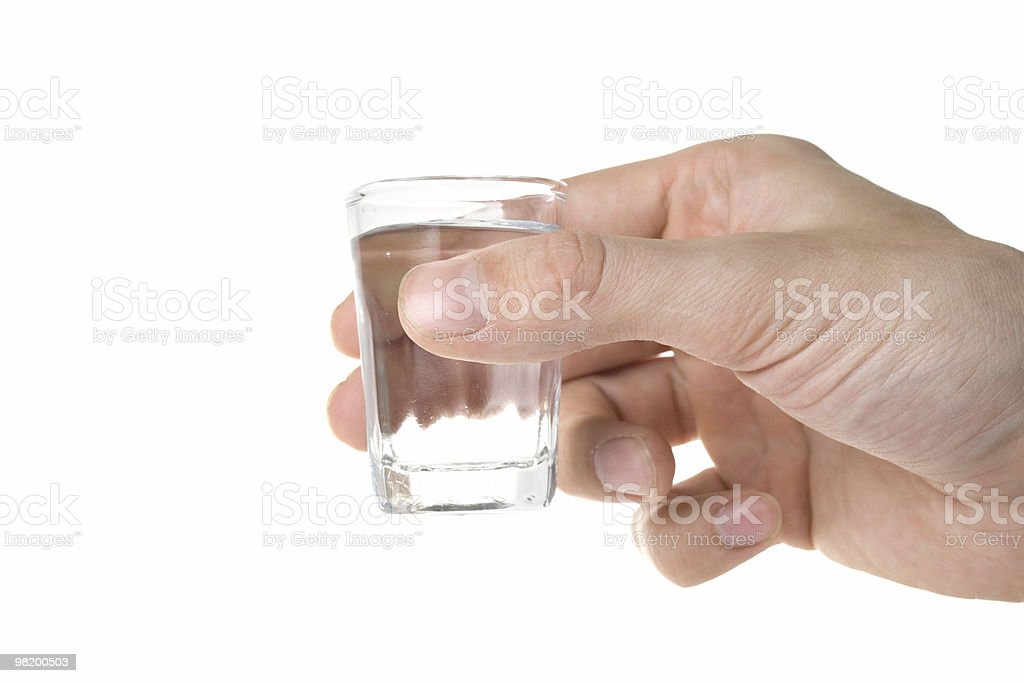 Hand holding a glass with vodka. royalty-free stock photo
