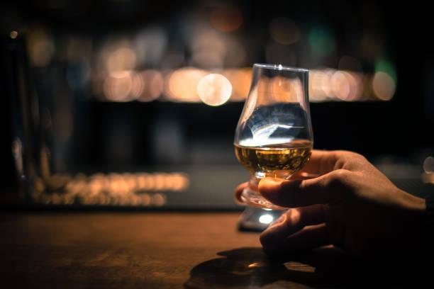 Hand holding a Glencairn single malt whisky glass stock photo