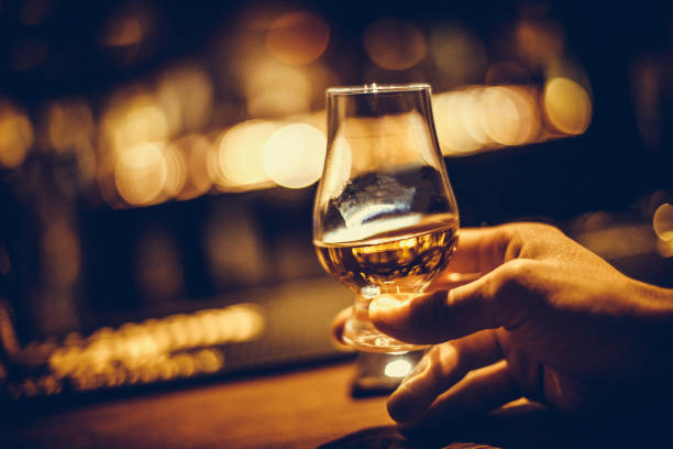 hand holding a glencairn single malt whisky glass - assaggiare foto e immagini stock
