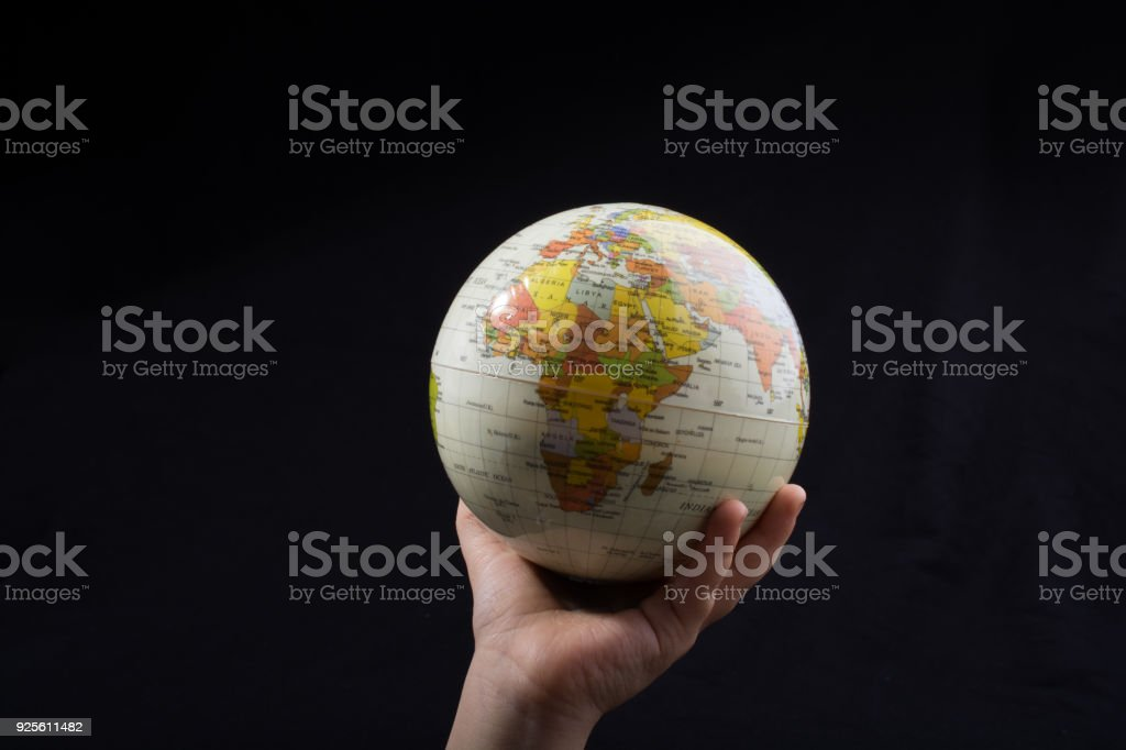 Hand holding a globe  with the map on it stock photo