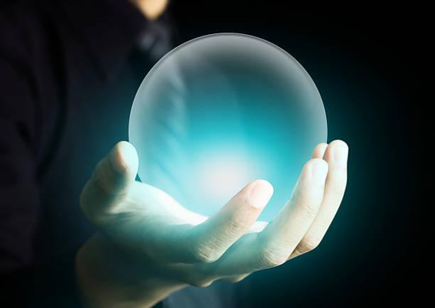 main tenant un ballon de cristal éclatant - boule de cristal photos et images de collection