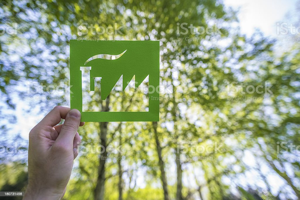 Hand holding a green factory against forest stock photo