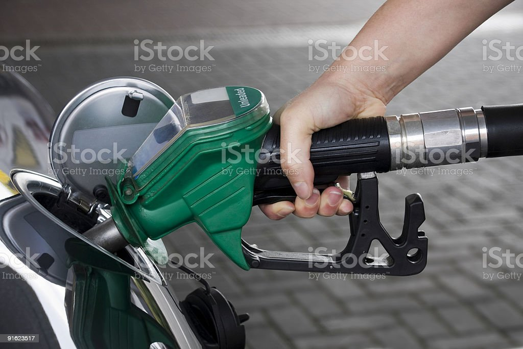 A hand holding a green gas pump in a cars fuel tank stock photo