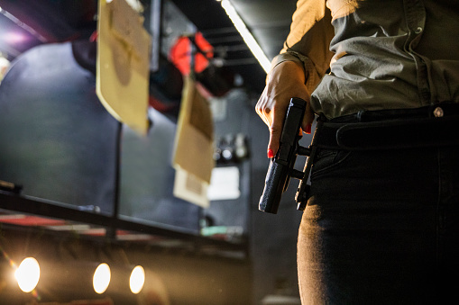 Close-up of woman's hand holding a gun at shooting range