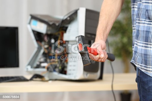 593328060istockphoto Hand holding a hammer after destroy a computer 536675834