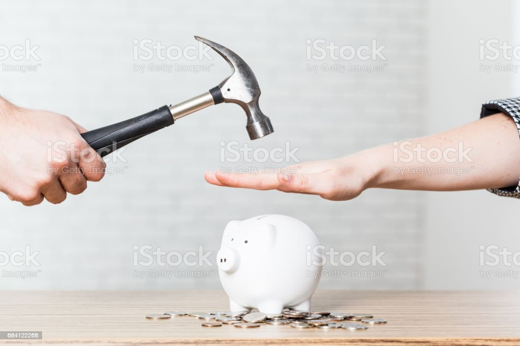 A hand holding a hammer which is raised above a white piggy bank stock photo