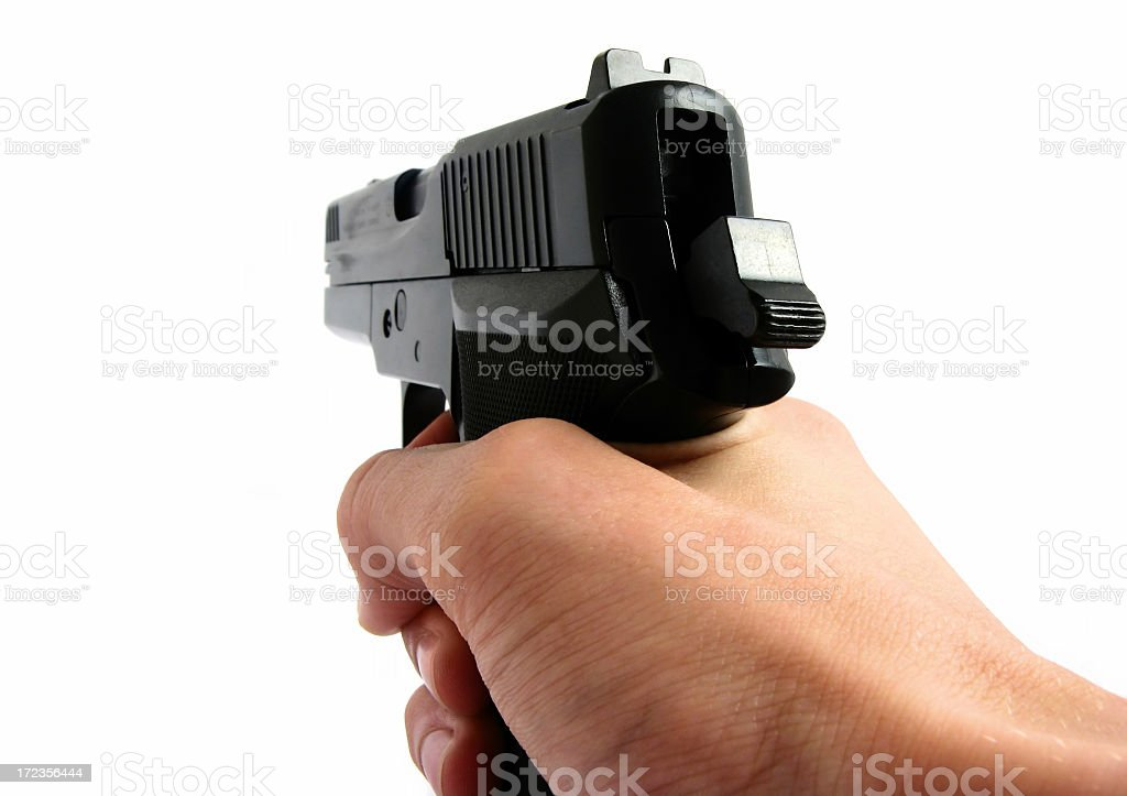Hand holding a handgun and pointing it into the distance royalty-free stock photo