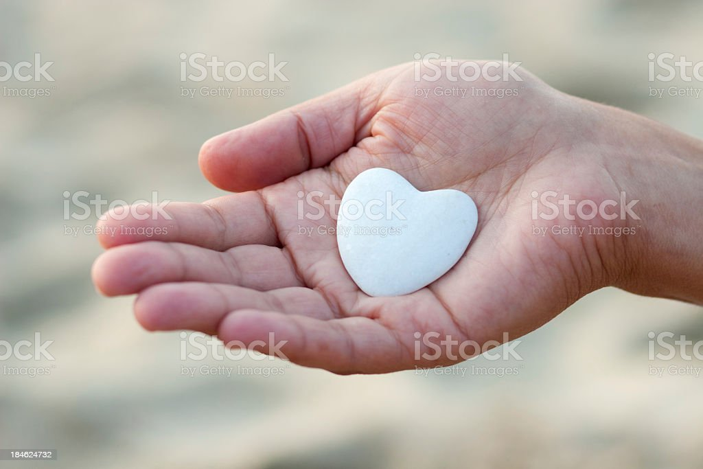 Hand holding a heart shaped stone stock photo