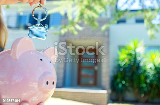 1048402108istockphoto Hand holding a house key and piggy bank in front of a large house. 919387194
