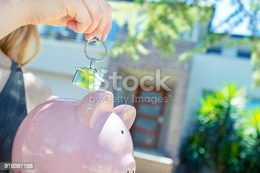 1048402108istockphoto Hand holding a house key and piggy bank in front of a large house. 919387198