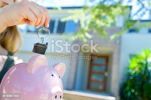 1048402108istockphoto Hand holding a house key and piggy bank in front of a large house. 919387200