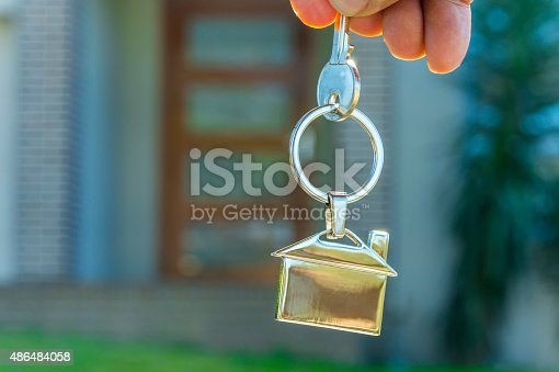 istock Hand holding a house key in front of a house. 486484058