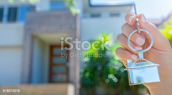 istock Hand holding a house key in front of a large house. 918374518