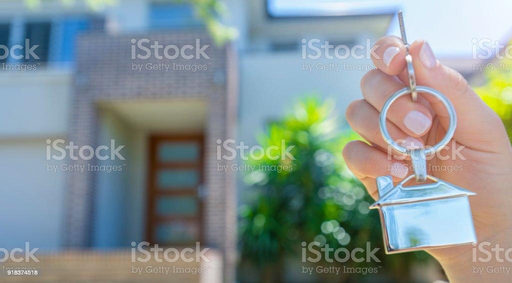 Hand, die einen Hausschlüssel vor einem großen Haus. – Foto