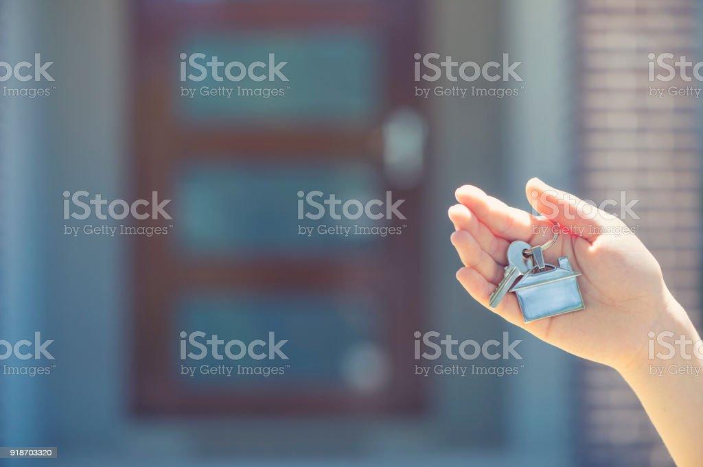 Mano sosteniendo una llave de la casa frente a una casa grande. - foto de stock