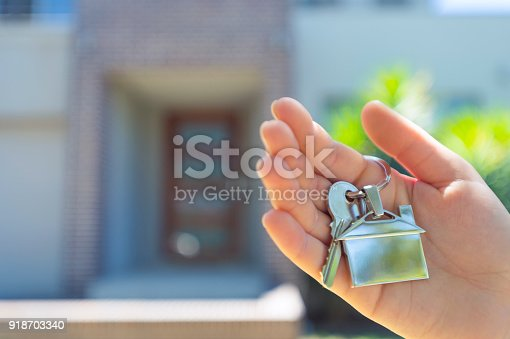 Hand holding a house key in front of a large house. The key ring has a house shaped icon on the end and is shiny silver colour. You can see the front door in the background. The key ring house icon is dangling down. Close up with shallow focus and copy space. New house concept.