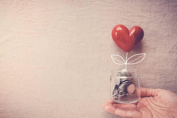 ręka trzyma słoik drzewa serca rosnącego na monetach pieniężnych, odpowiedzialności społecznej i koncepcji darowizny - plecy zdjęcia i obrazy z banku zdjęć