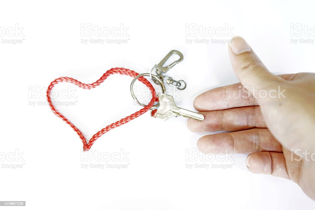 Hand holding a key with Red strap Heart-Shaped royalty-free stock photo