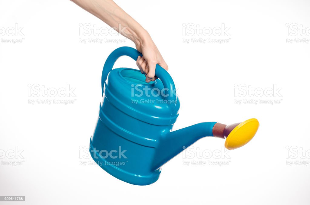 hand holding a large blue plastic watering can stock photo